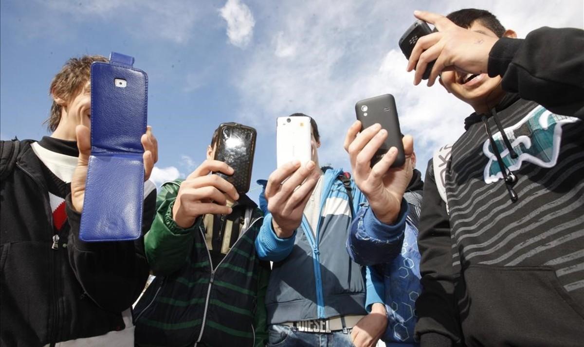 Adolescentes consultan redes sociales en el móvil.