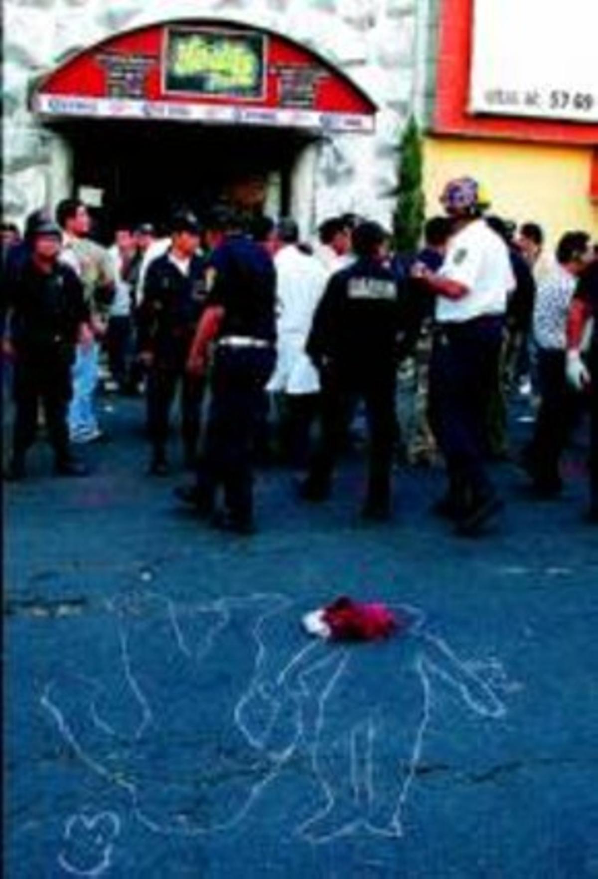 Policies parlen davant les siluetes a terra de dos dels cadàvers.
