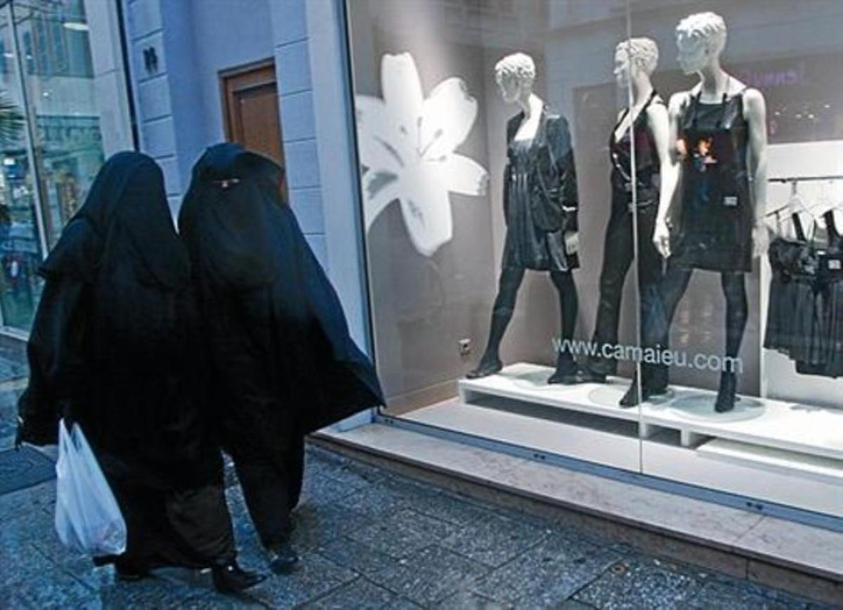 Dos mujeres con velo integral, ante un escaparate de ropa en Marsella.