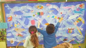Dos niños observan un mural que pintaron en clase para retratar la variedad de especies que existen en el fondo del mar.