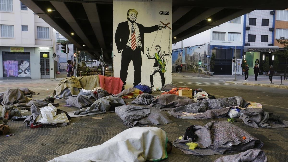 Un grupo de sin techo duerme bajo un puente de Sao Paulo ante una pintada de Bolsonaro como marioneta de Trump.