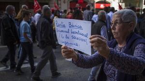Una manifestante reclama la renta básica universal.