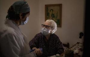 En tiempos de coronavirus, una cuidadora ayuda a una anciana a incorporarse en su piso de Barcelona.