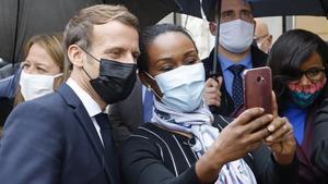 El presidente francés,Emmanuel Macron, se hace un 'selfie' con una vecina deLes Mureaux, al noroeste de París.