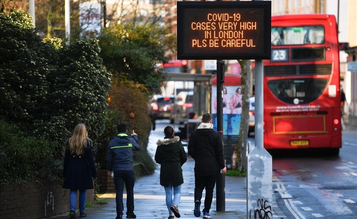 Mensaje de alerta sobre el elevado número de casos de covid-19 en una calle de Londres.