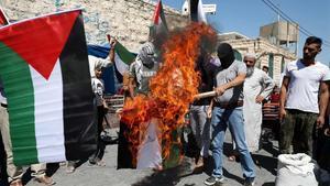 Manifestantes palestinos queman la bandera de EAU en la ciudad de Yata cerca de Hebrón.
