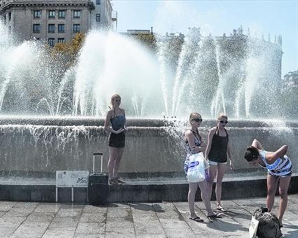 Varias personas se refrescan en las Fonts Bessones de la plaza de Catalunya, el pasado verano.