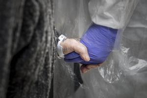 Un sanitario sostiene la mano de una persona mayor.