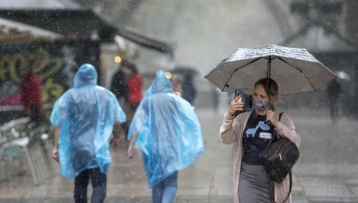 Paseantes por las Ramblas de Barcelona se protegen de la lluvia en 2020.