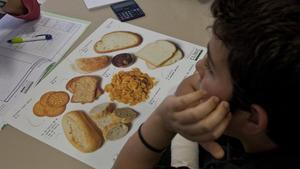 Un niño mira una cartulina en una imagen de archivo.