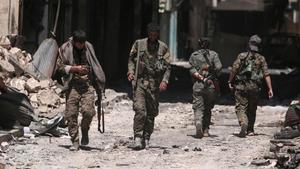 Combatientes de las Fuerzas Democráticas de Siria caminan sobre los escombros de tiendas y edificios dañados por la batalla en la ciudad de Manbij.