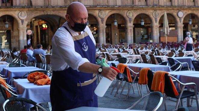 Un hostelero desinfecta las mesas de un bar de la Plaza Mayor de Salamanca, en una imagen de archivo