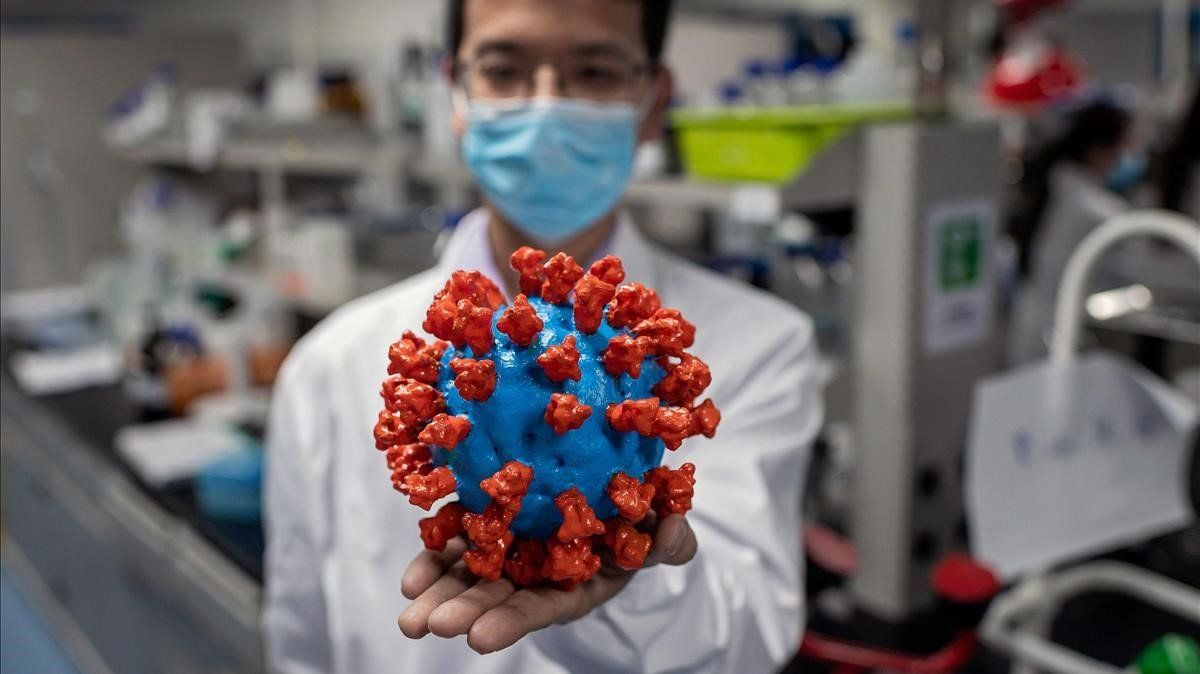 Un investigador muestra un modelo del virus en uno de los laboratorios de Sinovach, una de las empresas en busca de una vacuna