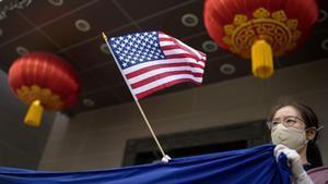 Un manifestante protestacon una bandera de EEUU frente al consulado de China en la ciudad de Houston.