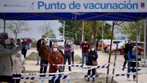Un grupo de personas  espera en el exterior del hospital Isabel Zendal para recibir la vacuna.