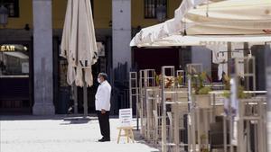 Ambiente de pocos o ningún turista en lugares icónicos de Madrid ,en la imagen un camarero espera clientes en la Plaza Mayor.