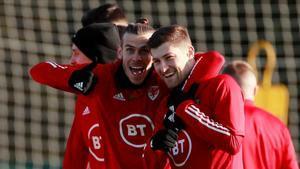 El madridista Gareth Bale (i) se abraza con Ben Davis en un entrenamiento de Gales de esta semana.