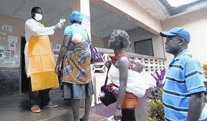 Un enfermero toma la temperatura a varias personas en el condado de Bomi, en Liberia.