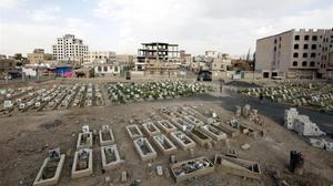 Yemenís caminan entre las tumbas con retratos de personas supuestamente asesinadas en combates en curso.