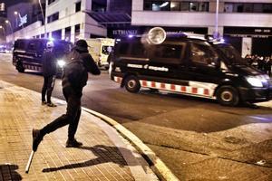 Un manifestante lanza un objeto del mobiliario urbano contra un furgón de los Mossos d'Esquadra, este viernes en Barcelona.