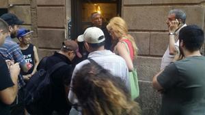Movilización vecinal frente a la puerta custodiada por un trabajador de la empresa de desolojos.