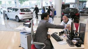 Un cliente de un concesionario de coches pide información.