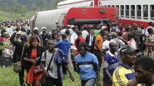 Pasajeros del tren descarrilado salen del lugar del accidente.