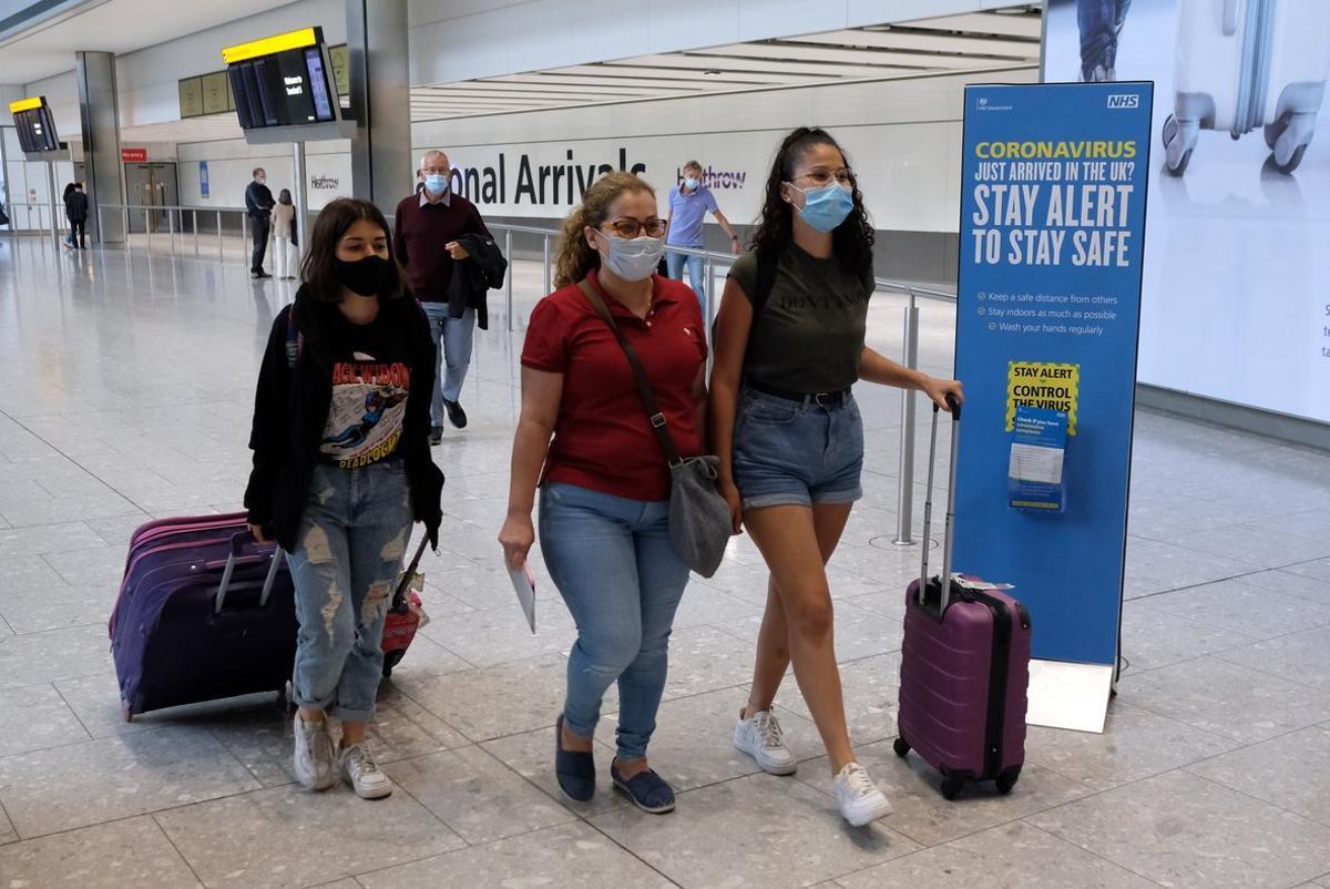 Tres jóvenes procedentes de Madrid llegan al aeropuerto de Heathrow, este domingo.