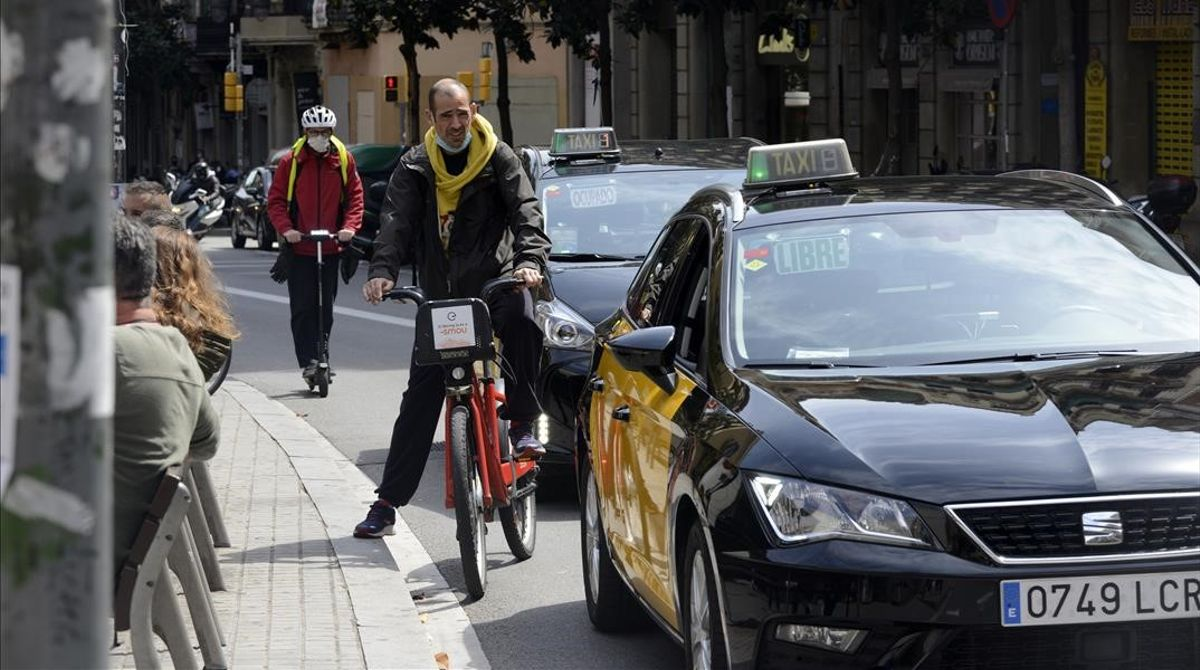 Un ciclista sortea el tráfico en la calle Gran de Gràcia de Barcelona.