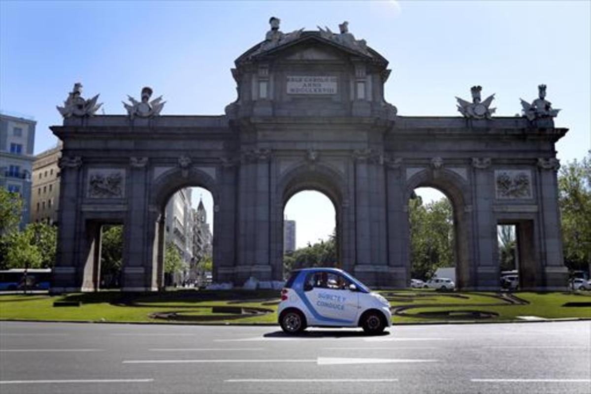 Un vehículo de Car2Go circula por la Puerta de Alcalá, en Madrid.