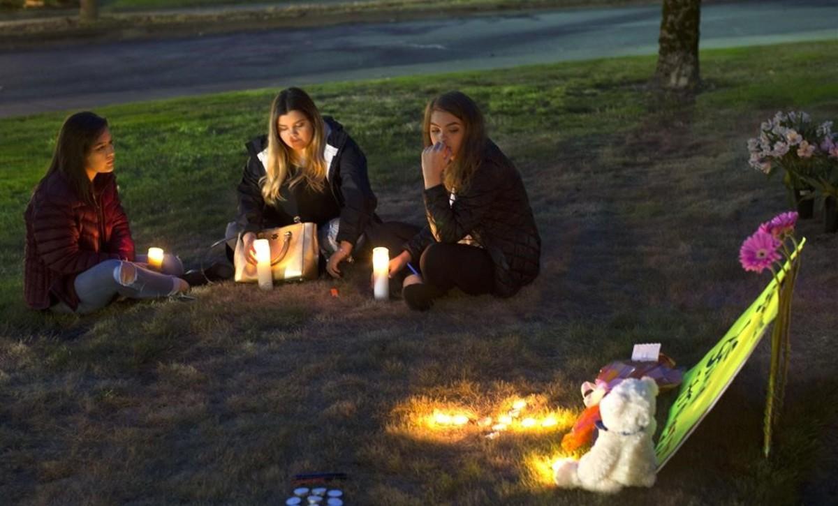 Unas jóvenes encienden velas en memoria de las víctimas del tiroteo en Burlington.