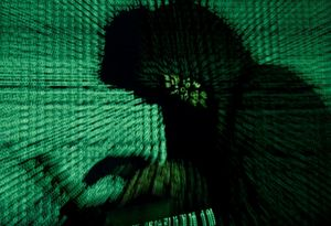 FILE PHOTO  A man holds a laptop computer as cyber code is projected on him in this illustration picture taken on May 13  2017  Capitalizing on spying tools believed to have been developed by the U S  National Security Agency  hackers staged a cyber assault with a self-spreading malware that has infected tens of thousands of computers in nearly 100 countries  REUTERS Kacper Pempel Illustration File Photo
