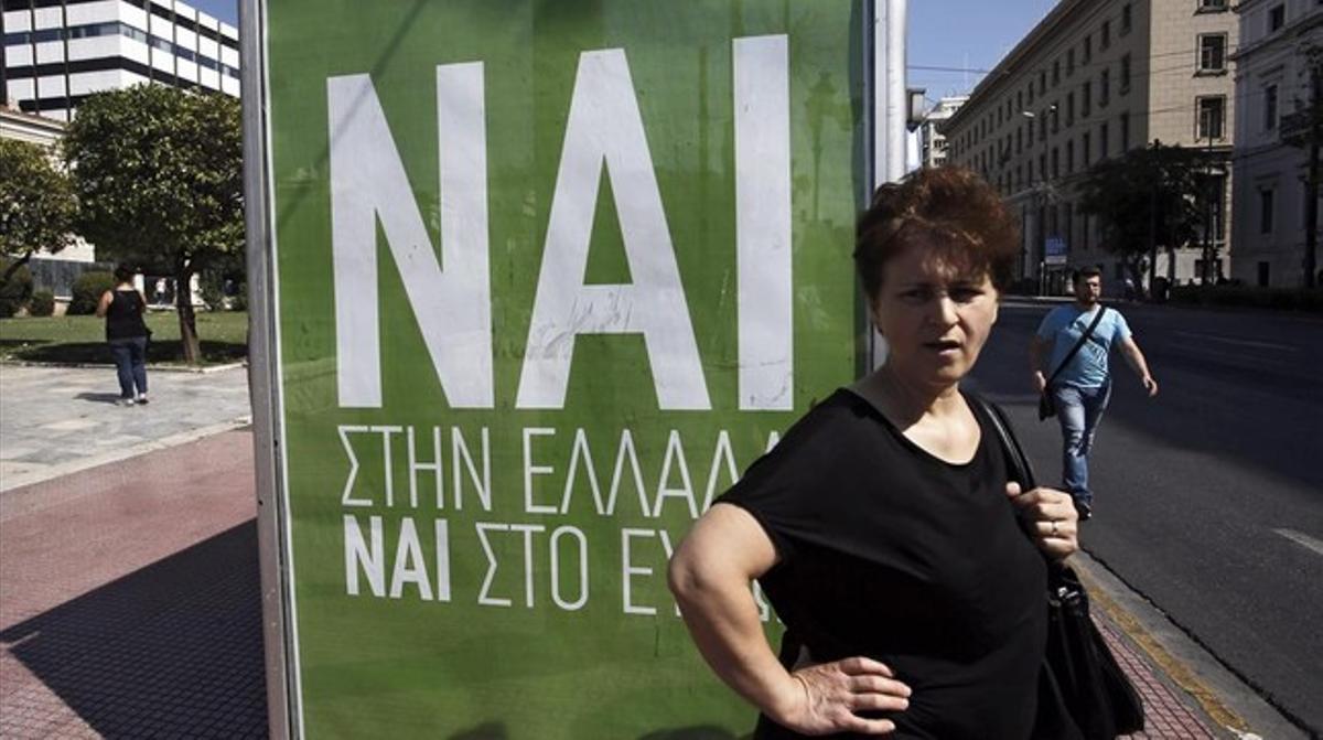 Una mujer espera el autobús junto a un cartel que pide el voto positivo en el referéndum, en el que se lee: Sí a Grecia, sí al euro.