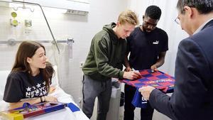 Frenkie de Jong firma una camiseta que sostienen Samuel Umtiti y Josep Maria Bartomeu, el presidente del Barça, en el Hospital de Nens.
