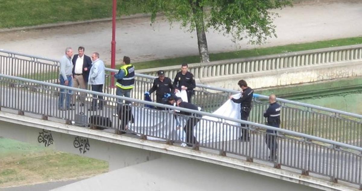 El cadáver de Isabel Carrasco tendido en la pasarela del río, donde la presidenta de la Diputación ha sido asesinada esta tarde.
