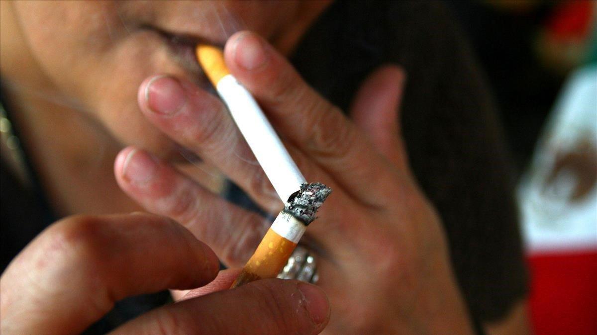 Una mujer enciende un cigarrillo con otro.
