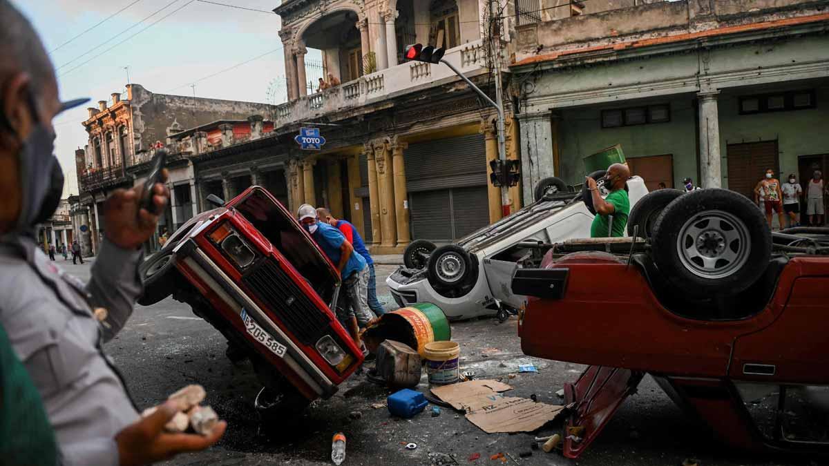 Coches de policía destrozados en las protesta ciudadanas en La Habana.