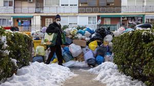 Decenas de bolsas de basura se acumulan en los cubos situados en las calles de Madrid tras las fuertes nevadas, este miércoles.
