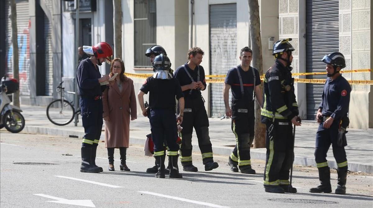 Los bomberos atienden las preguntas de una vecinas desalojadas.