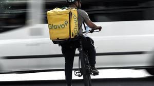 Un rider de la empresa de reparto de comida a domicilio Glovo, pasea por una calle de Madrid con su bicicleta en 2019.