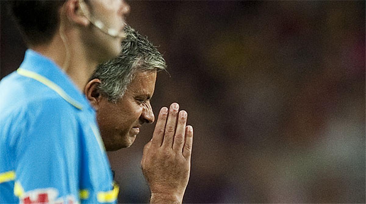 Mourinho fa un gest amb la mà davant el nas, com si Messi i Alves fessin pudor.