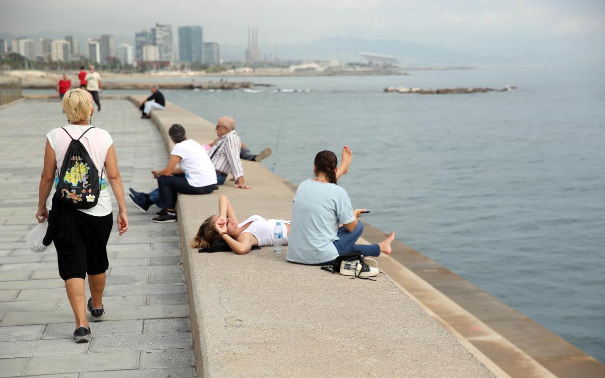 Gente descansando en la escullera del Poble Nou, en Barcelona.