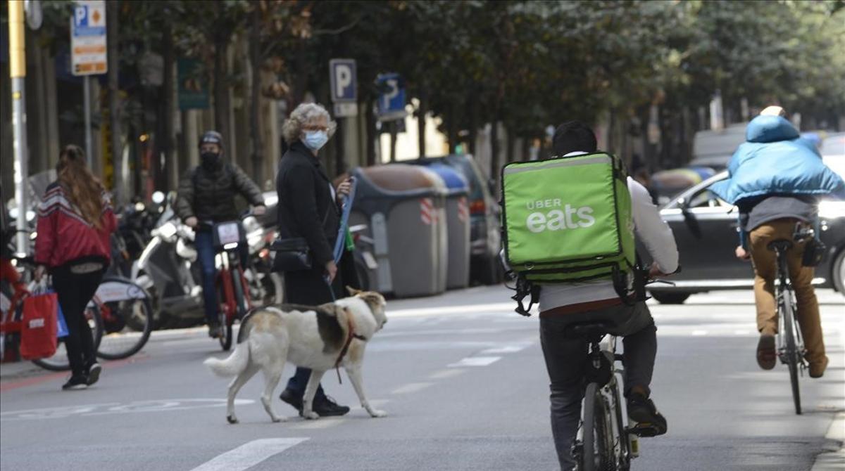 Una señora con su perro cruza por la calle de Gran de Gràcia mientras circulan varias bicicletas por el carril bus.