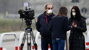 Reporteros que cubren el brote de coronavirusaguardan informaciones provistos de mascarilla.