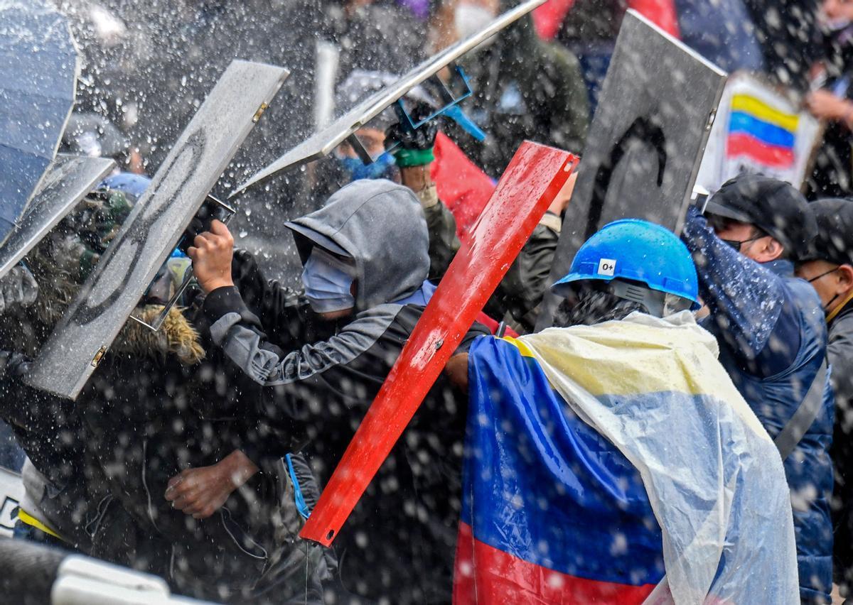Manifestantes se enfrentan a la policía durante la protesta de este miércoles en Bogotá.