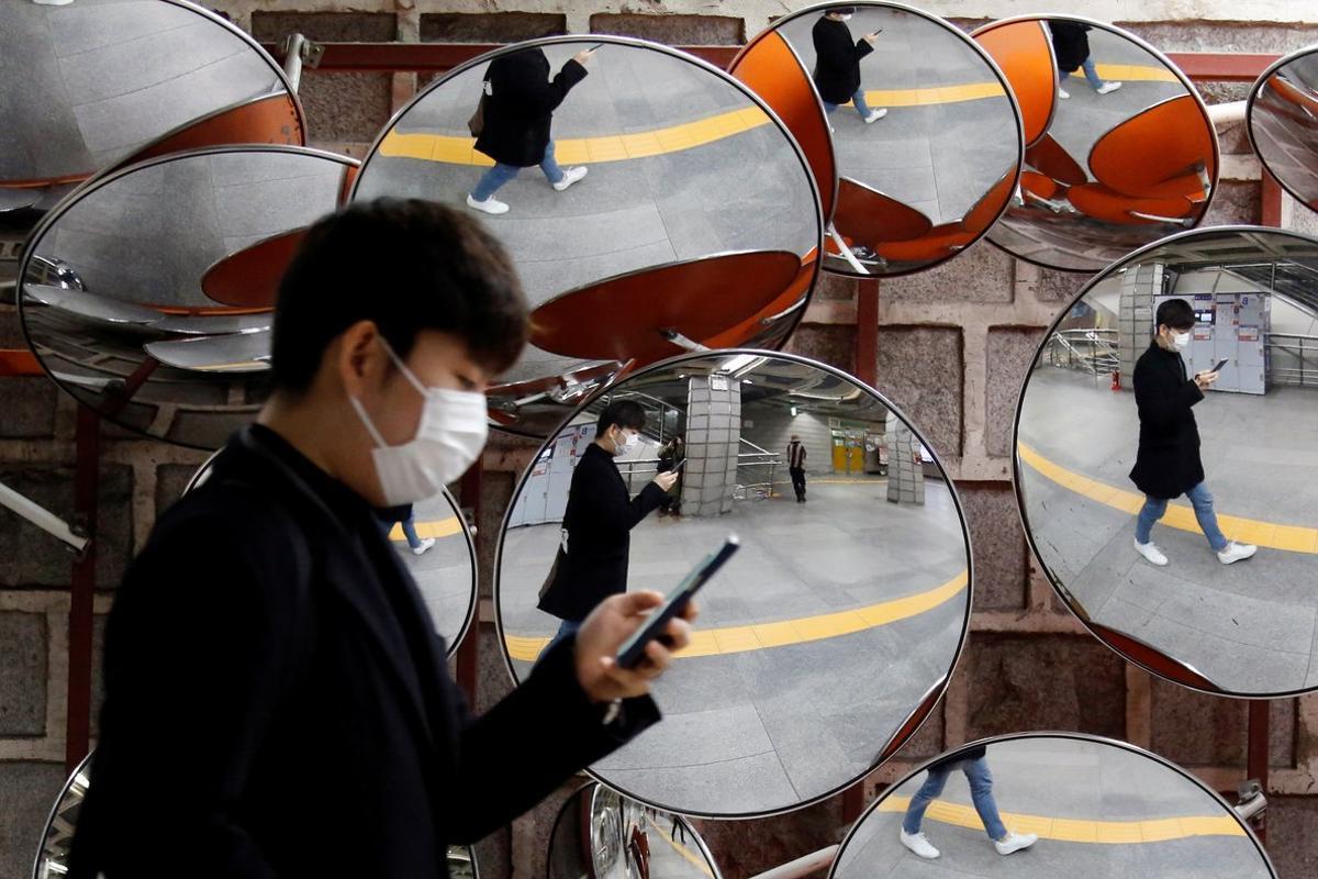 Un ciudadano coreano pasea protegido por las calles de Seúl.