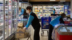 Trabajadores en un supermercado Caprabo.