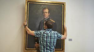Un operario retira el retrato del rey emérito, Juan Carlos I, de la Sala de Gobierno del Legislativo Foral del Parlamento de Navarra, el pasado 15 de junio.