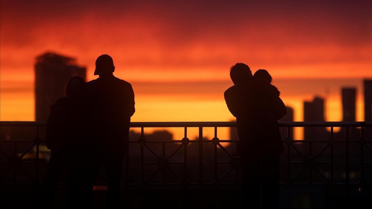 Varias personas contemplan la puesta de sol en Moscú desde un mirador