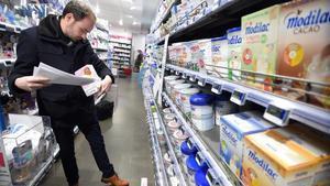 Un trabajador del Gobierno francés inspecciona productos de Lactalis en una farmacia.